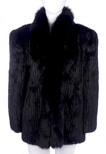 A black ribbed mink jacket with fox fur trim. Designed with a short full Mandarin collar, hook and e