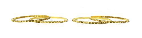 A set of four Indian high carat gold bangles,