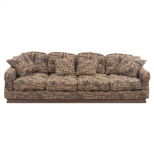 Sofá de 4 plazas. SXX. Estructura de madera con tapicería de tela en tono café con acojinados y soporte tipo zócalo.