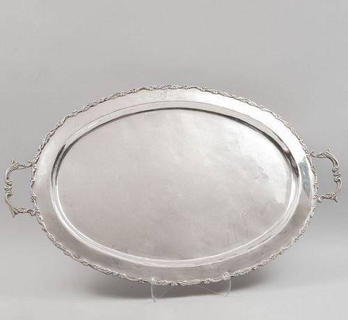 Charola. SXX. Elaborada en plata Sterling, Ley 0.925 sellada PLATERÍA F.M. Diseño oval. 4 puntos de soporte. 46 x 74 cm. 2523 g