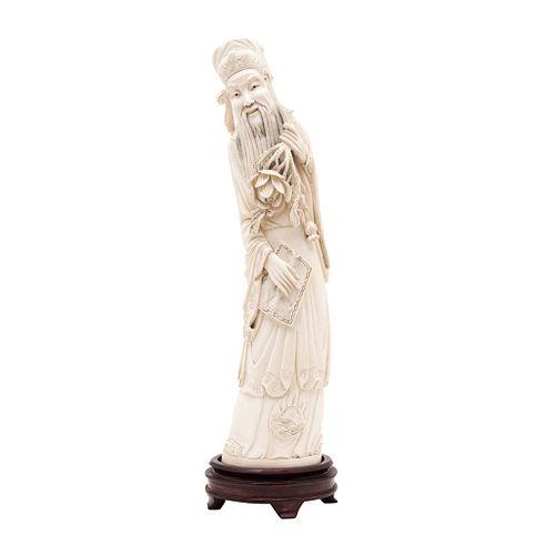 HOMBRE SABIO CON FLORES. CHINA, SIGLO XX. Talla marfil con detalles en tinta. Firmado en la parte inferior con una imagen. 39 cm alt. | WISE MAN WITH