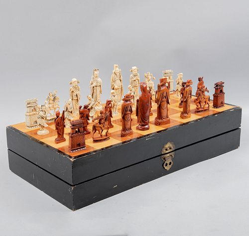Juego de ajedrez. China, SXX. Talla en marfil acabado crudo y cinabrio. Estuche abatible de madera para tablero. 60 x 14 x 30 cm.
