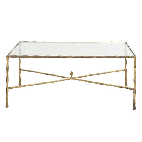 """Mesa de centro. SXX. Estructura de metal dorado y cubierta rectangular de vidrio. Chambrana en """"X"""", fustes y soportes amoldurados."""