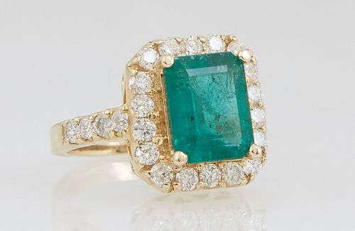Lady's 14K Yellow Gold Dinner Ring, with a 2.97 carat emerald atop a conforming border of round diamond, the shoulders of the band also mounted with r