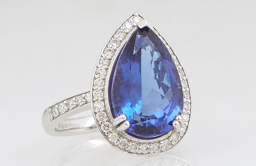 Lady's Platinum Dinner Ring, with a pear shaped 7.84 carat tanzanite, atop a conforming border of small round white diamonds, the shoulders of the ban