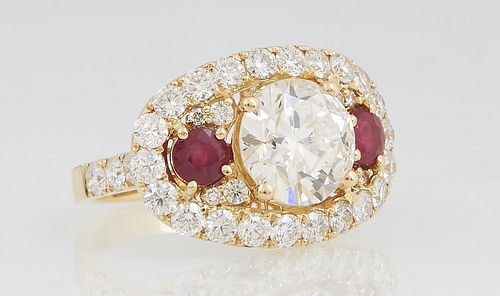 Lady's 18K Yellow Gold Dinner Ring, with a central 2.9 carat round diamond, flanked by two round rubies, within an oval border of round white diamonds