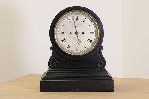 A black marble drumhead mantel clock,