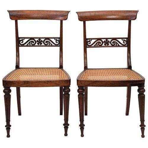 PAR DE SILLAS Ca. 1900 En madera tallada, con asientos en bejuco Detalles de conservación 85 cm de alto | PAIR OF CHAIRS Ca. 1900 In carved wood, seat