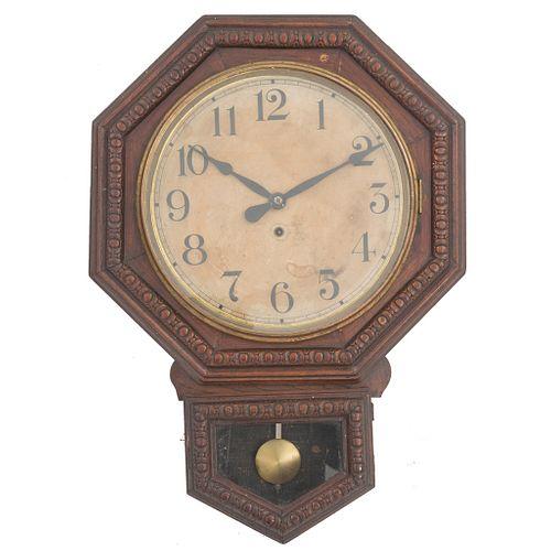 Reloj de pared. Estados Unidos, SXX. Estilo Art Decó. Elaborado en madera. Diseño octagonal. Carátula circular, índices arábigos.