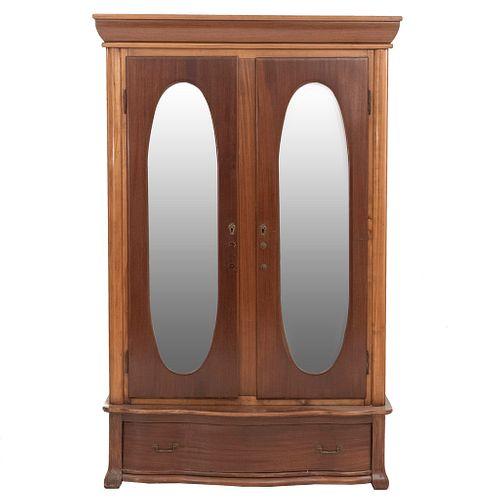 Armario. SXX. Elaborado en madera. 2 puertas con espejo de luna oval biselada, espacio para entrepaños, cajón y soportes semicurvos.