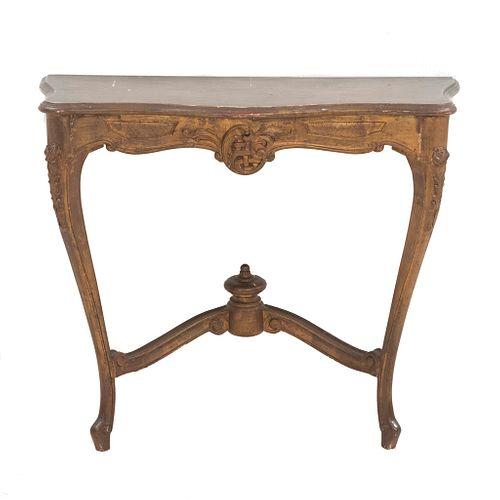 Mesa consola. SXX. Estilo Luis XV. Elaborada en madera dorada. Cubierta irregular y soportes semicurvos. Decoradas con molduras.