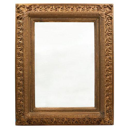 Espejo. Origen europeo, principios del SXX. Elaborado en madera dorada y estucada. Con luna rectangular. Decorado con molduras.