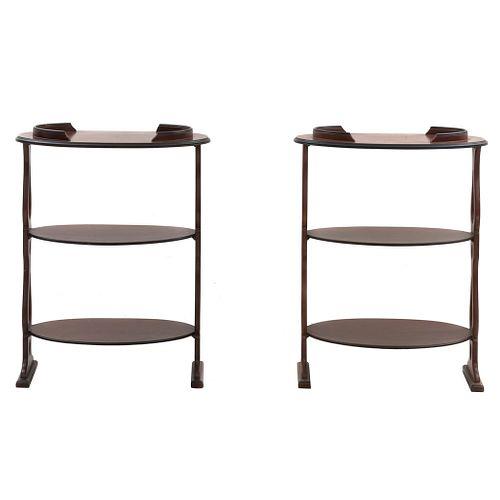 Par de mesas auxiliares. SXX. Elaborado en madera enchapada. A 3 niveles, cubiertas ovales y soportes tipo caballete.