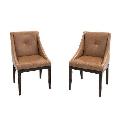 Par de sillones. SXX. Estilo danés. Estructura en madera. Respaldos y asientos con tapicería de vinipiel y soportes lisos.