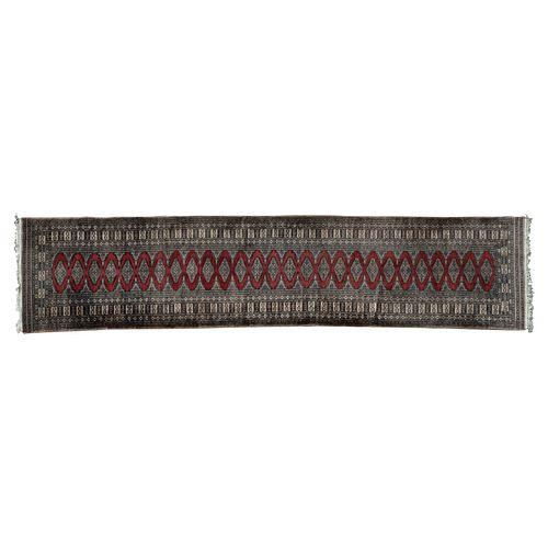 Tapete de pasillo. Origen oriental, SXX. Estilo Bokhara. Elaborado en fibras de lana y algodón. Decorado con motivos geométricos.
