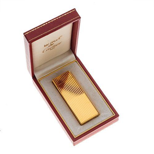Encendedor Cartier Must. Cuerpo en acero plaque. Diseño acanalado. Estuche original.