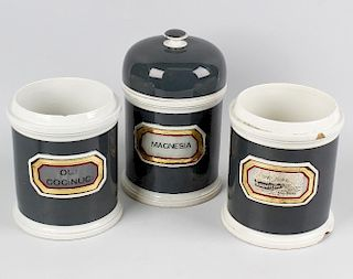 Seven late Victorian pottery apothecary jars, each of cylindrical form with dark green glazed ground