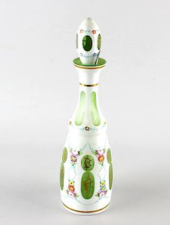 A Bohemian overlay glass bottle and stopper, of green glass having white overlay decorated with flor