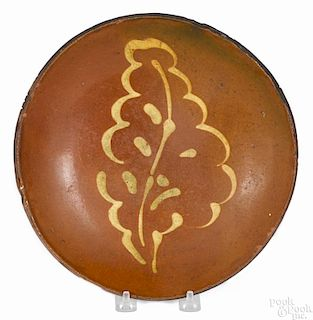 Pennsylvania redware plate, 19th c., with yellow slip leaf decoration, 10'' dia.
