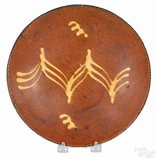 Two Pennsylvania redware plates, 19th c., with yellow slip decoration, 9 3/4'' dia. and 10'' dia.