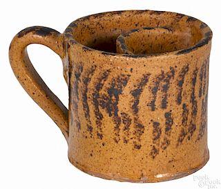 Pennsylvania redware shaving mug, 19th c., with manganese striped decoration, 3 1/2'' h.