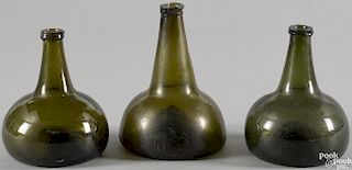 Three blown olive glass squat bottles, late 18th c., 6 1/2'' h., 7 3/4'' h., and 6 3/4'' h.