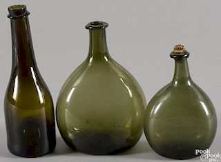 Two olive green blown glass bottles, early 19th c., together with a dark amber bottle
