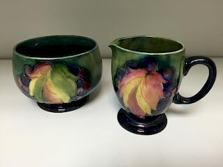 A Moorcroft leaves and berries pattern milk jug and sugar basin, decorated to a green ground painted