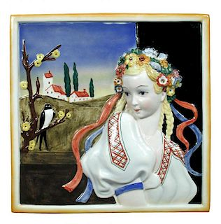 Attributed to Lenci, a porcelain plaque, decorated in relief with a maiden, a church behind and a bi