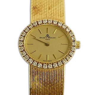 Lady's Vintage Baume & Mercier 14 Karat Yellow Gold Bracelet Watch with Diamond Bezel.
