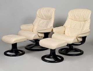 PAIR OF HJELLEGJERDE SWIVEL ARM CHAIRS AND FOOTSTOOLS