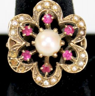 14k y.g. floral form ladies ring having center 7mm luster pearl. 6 sm round cut rubies and small see