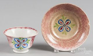 Red spatter cup and saucer with a four-petal flower decoration.