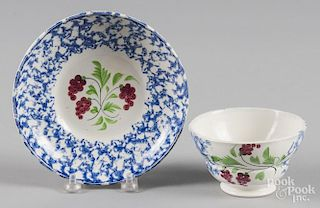 Blue sponge cup and saucer with berry decoration.