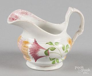 Yellow and red rainbow spatter creamer with thistle decoration, 4 1/4'' h.