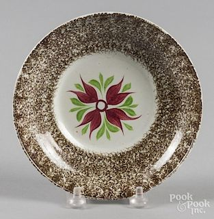 Brown spatter saucer with a four-petal flower decoration.