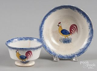 Blue spatter cup and saucer with rooster decoration.