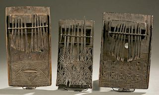 2 thumb pianos with carved linear motifs.