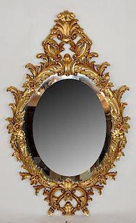 Ornate gilt oval mirror