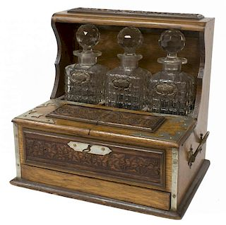 ARTS & CRAFTS OAK TANTALUS WITH THREE DECANTERS