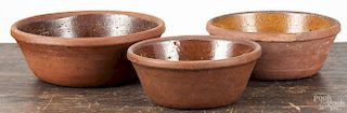 Nest of three Pennsylvania redware bowls, 19th c., largest - 3 3/4'' h., 10'' dia.