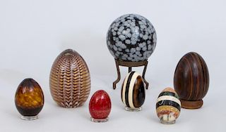 THREE GLASS EGGS, AN INLAID MARBLE EGG, A WOOD EGG, A MARBLEIZED EGG AND A DOTTED EGG