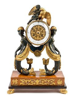 * An Austrian Carved and Parcel Gilt Empire Mantel Clock Height 22 x width 15 1/4 inches.