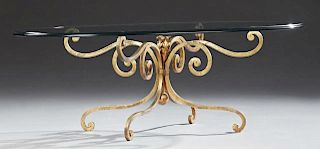 French Glass and Wrought Iron Coffee Table, 20th c., the thick oval beveled edge top on a gilt scrolled wrought iron base on