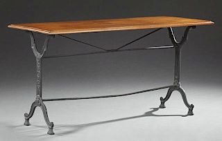 French Carved Oak and Cast Iron Bistro Table, 19th c., the rectangular top on cast iron trestle supports joined by cylindrica