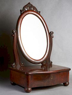 American Carved Mahogany Shaving Mirror, late 19th c., the oval mirror with a scrolled surmount, on curved reeded supports to