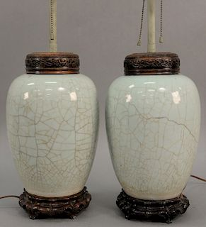 Pair of Chinese crackle glazed jars having light blue color with carved hardwood cover and stand, made into table lamps. height 24 i...