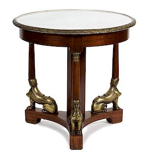 An Empire Style Gilt Metal Mounted Mahogany Center Table Height 31 x diameter of top 32 1/2 inches.