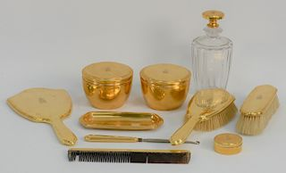 Tiffany & Co. 18 karat gold ten piece dresser set,  two covered gold jars, a pin tray, a small gold round box, hand mirror, two brus...