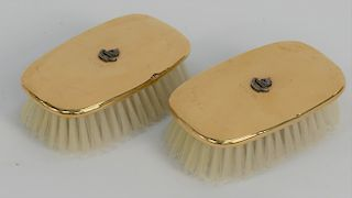 Three piece 14 karat gold lot to include a pair of 14 karat gold brushes,  mounted with silver family crest, initialed J.J.S., and a...